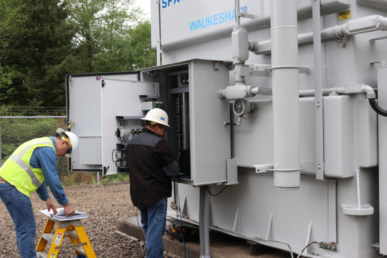 Men working to prepare transformer